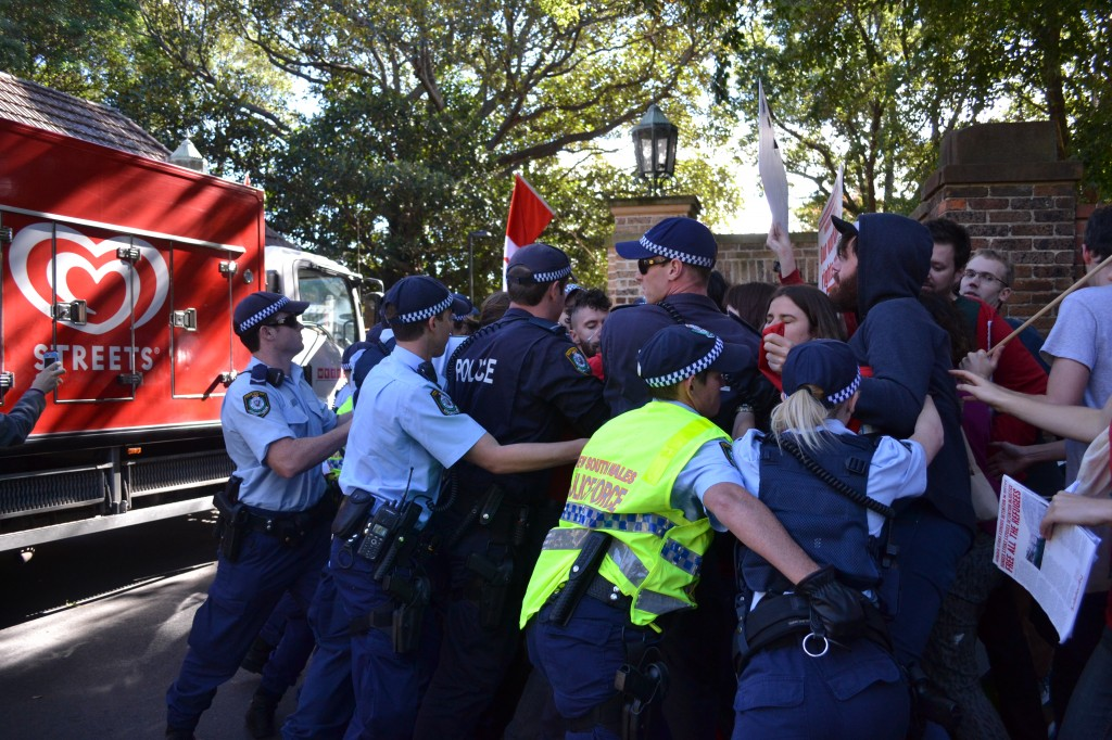 Police push protesters out of the way of a delivery van