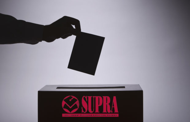 A silhouetted hand holding a ballot over a box labelled SUPRA
