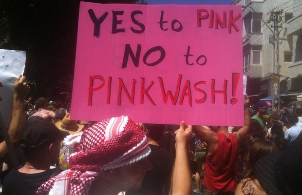 People hold a sign protesting pinkwashing.