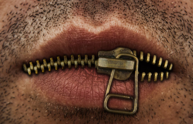 Man's lips covered with zipper.