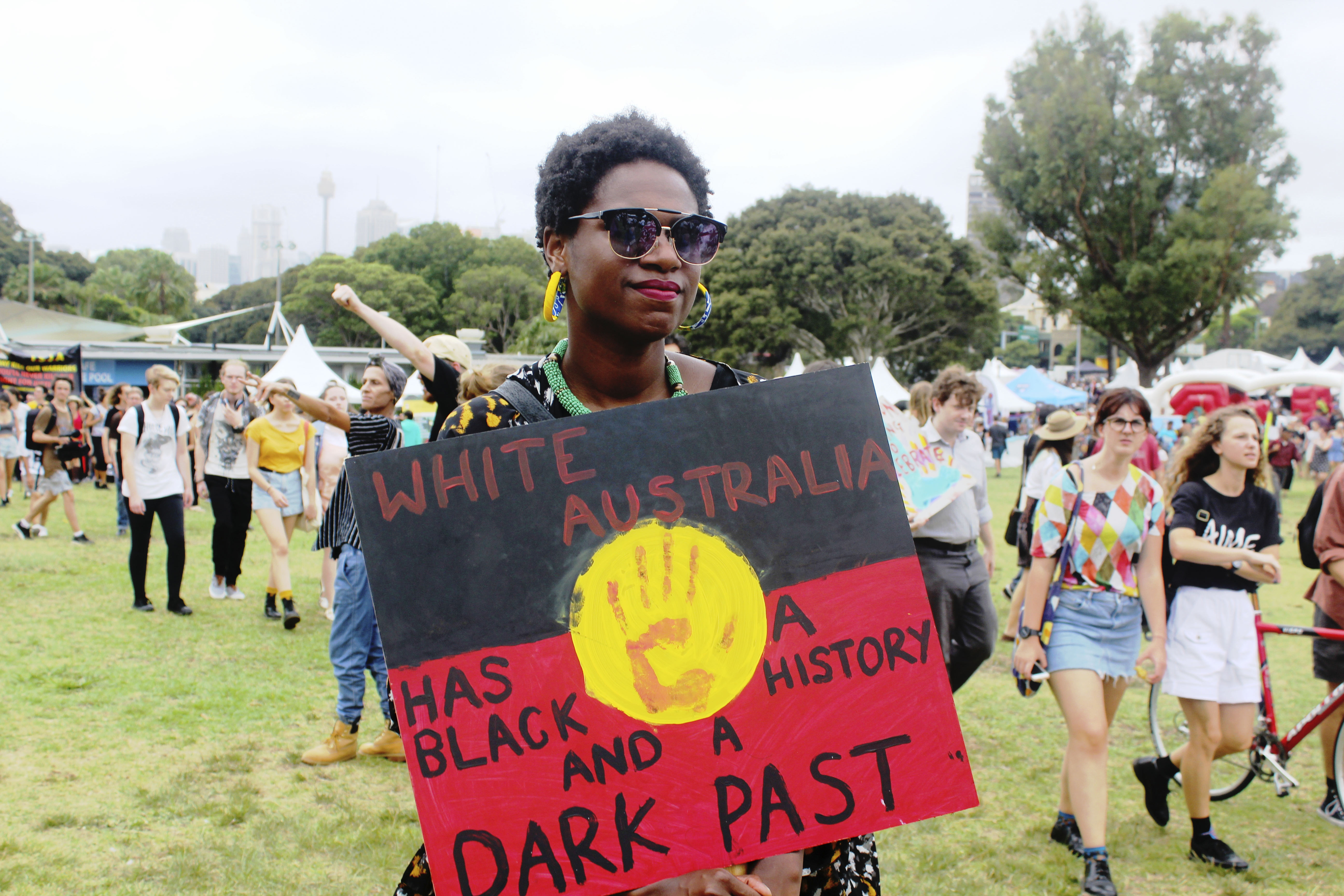 Protester holds sign reading 'white Australia has a black history and a dark past'.