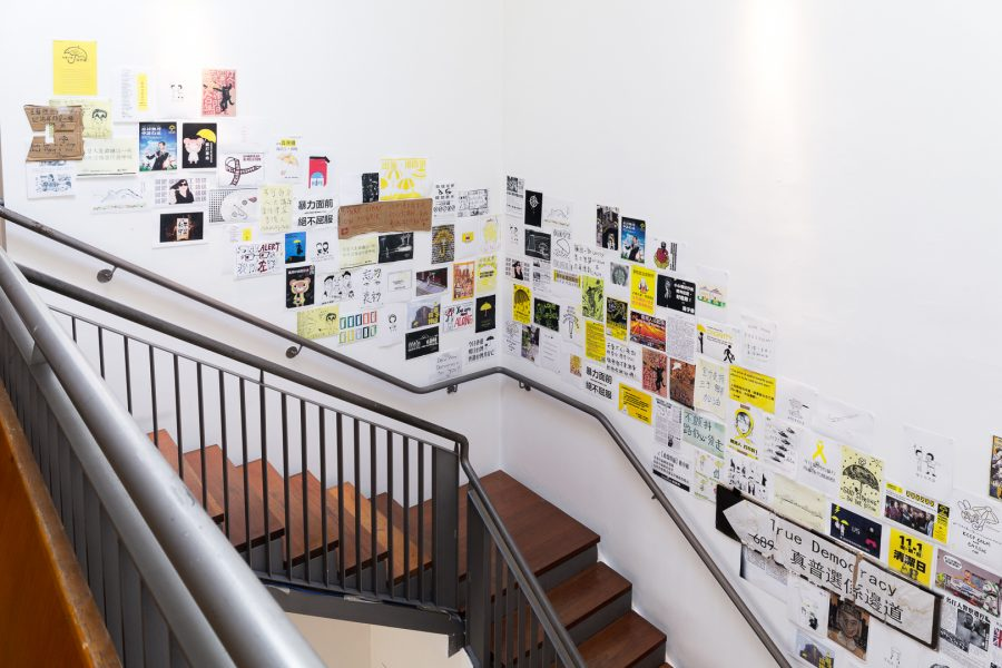 The stairs in the split-level gallery, with documentary photos of the Umbrella Movement lining its walls.