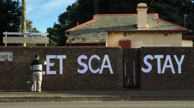 Protester painting 'Let SCA Stay' on the brick wall surrounding the Sydney College of the Arts.