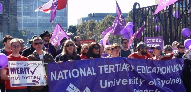 NTEU protestors waving small purple flags and carrying a purple National Tertiary Education Union banner