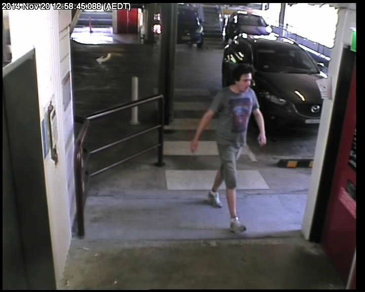 A man in a dark grey shirt walking towards the exit of a car park. In the top and bottom right hand corners there are time and location stamps from the CCTV footage from which this still has been taken.