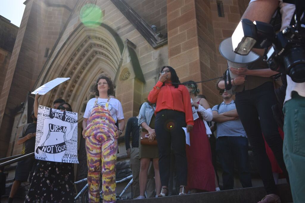 Greens MP Mehreen Feruqi standing at the top of St Mary's Cathedral's steps with a group of brightly coloured protestors, who are holding hand-painted signs and megaphones