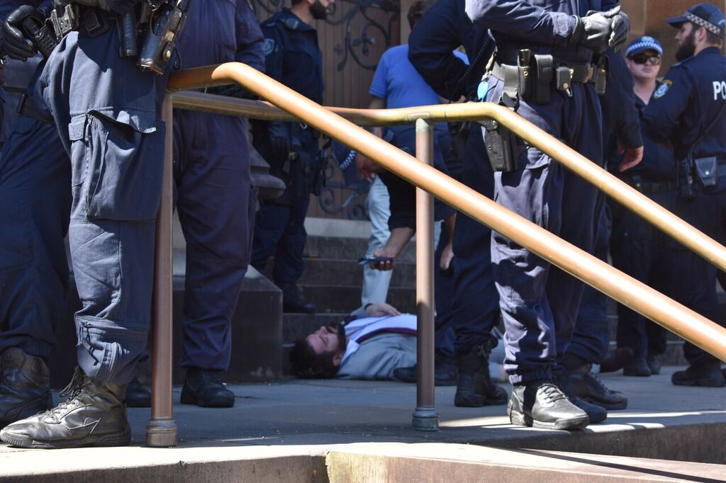 A man, part of the Church's congregation, lies on the Cathedral steps, with police starting to circle around him. A police man hovers over him, taking photographs of him.