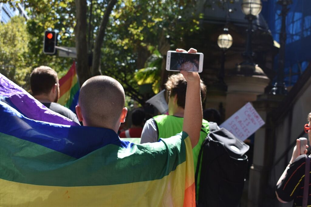 A protestor, walking ahead of the camera, with a shaven head is wrapped in a rainbow flag. In her right hand, she is holding her iPhone and is visibly Facebook Live Streaming herself marching in the protest.