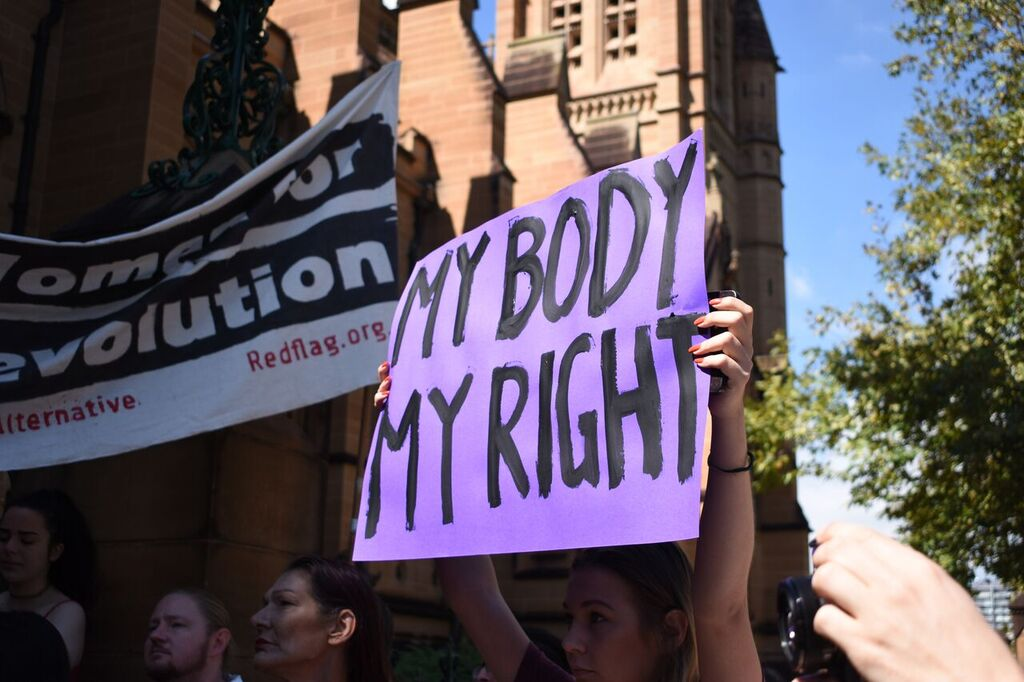 "Protestor holding up a hand-painted, purple poster that reads: ""My body my right"", in front of St Mary's Cathedral"