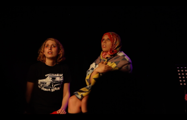Two women standing in the light against a dark background onstage