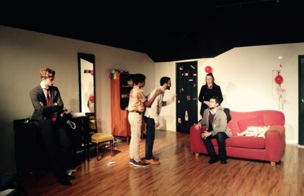 Five people on a theatre set. One is leaning on a dark cabinet, two are standing in the middle of the room, one is sitting on the red couch and the last is standing behind the couch. One of the men in the middle of the room is shouting at the one seated on the couch.