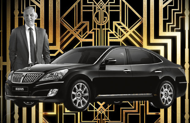 Photograph of Michael Spence, looking happy, photoshopped standing next to a fancy black car. In the background is an image is the 20's Art Deco print from the Great Gatsby movie in black and gold.