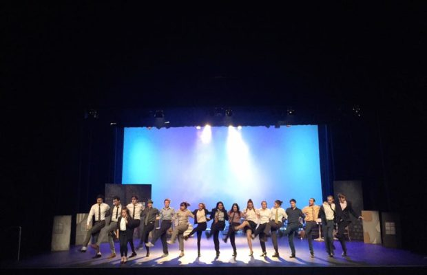 A line of performers from Commerce Revue doing high kicks on stage