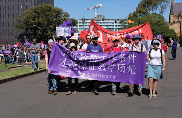Group of staff and students marching with a purple strike banner written in Chinese Characters.