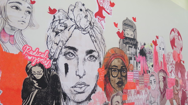 Maryam's portrait, by Molly Crabapple, on the left. Artwork by Ms Saffaa and collaborators.