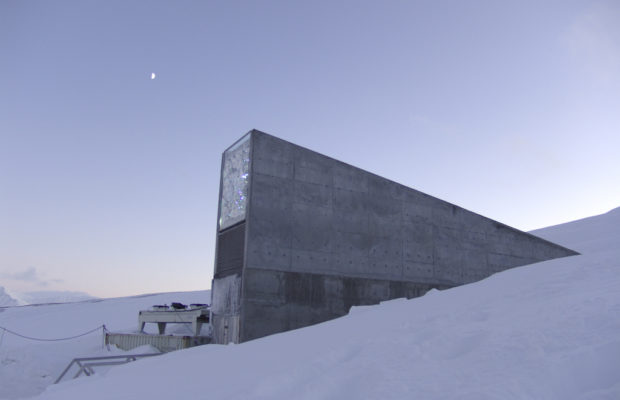 A large concrete building jutting out of the snow; it is dusk.