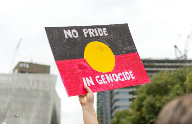 "A ""No Pride in Genocide"" sign held aloft. Photo credit: Connor Parrisis"