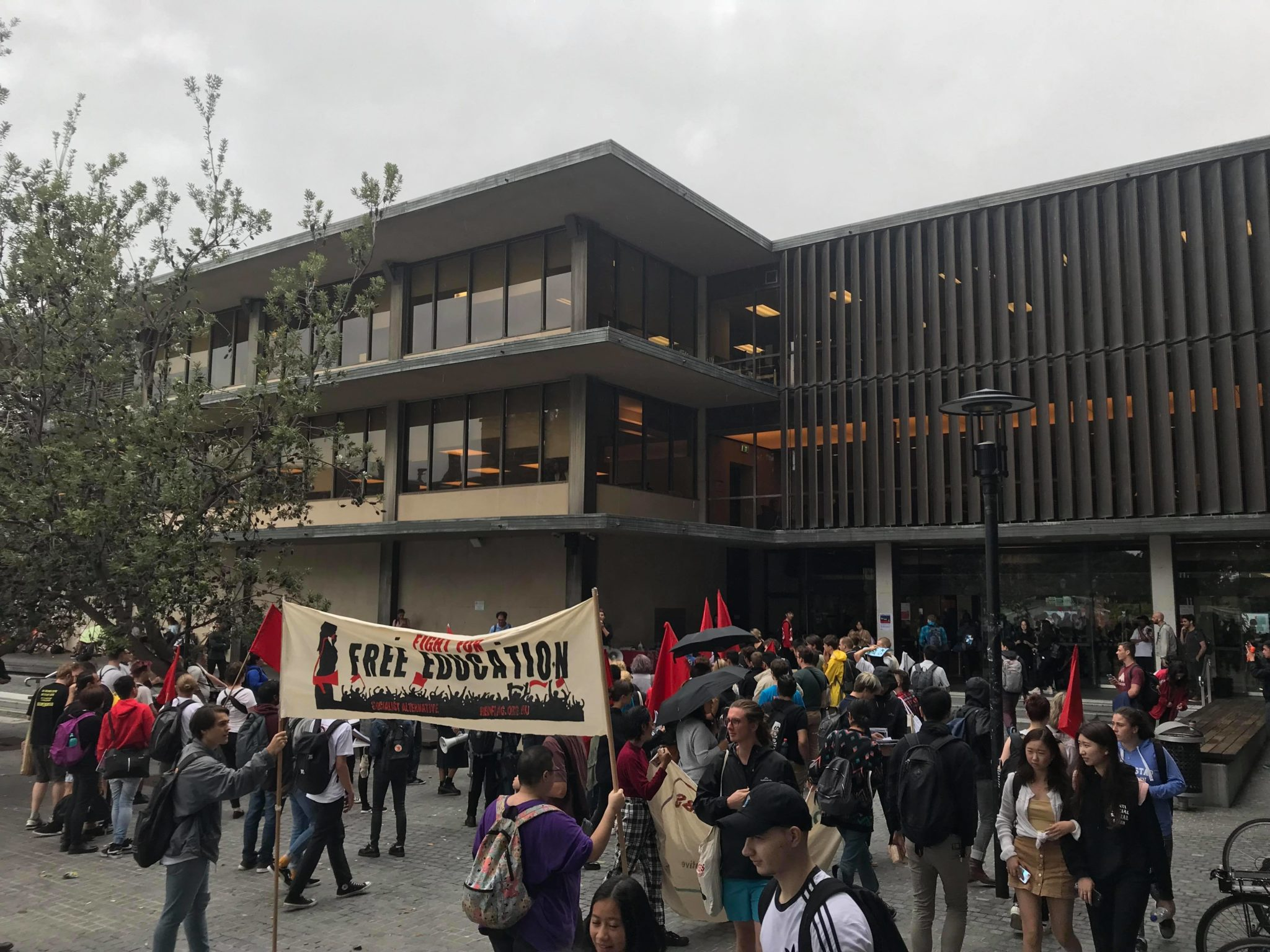Image: protestors begin to assemble out the front of Fisher Library at the University of Sydney.