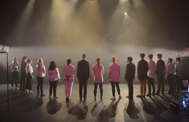 Group of performers onstage, standing in line, backs facing camera, lit by stage lights