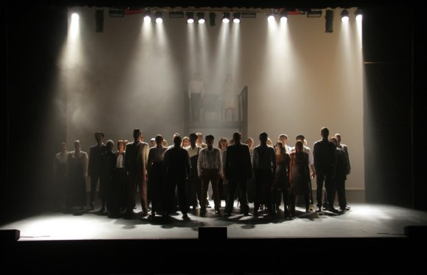 Full cast stands singing choral number on shadowy stage, downlight providing spot illumination.