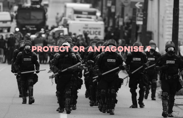 "Black and white image of police in riot squad gear, text overlayed in light pink which reads ""PROTECT OR ANTAGONISE?"""