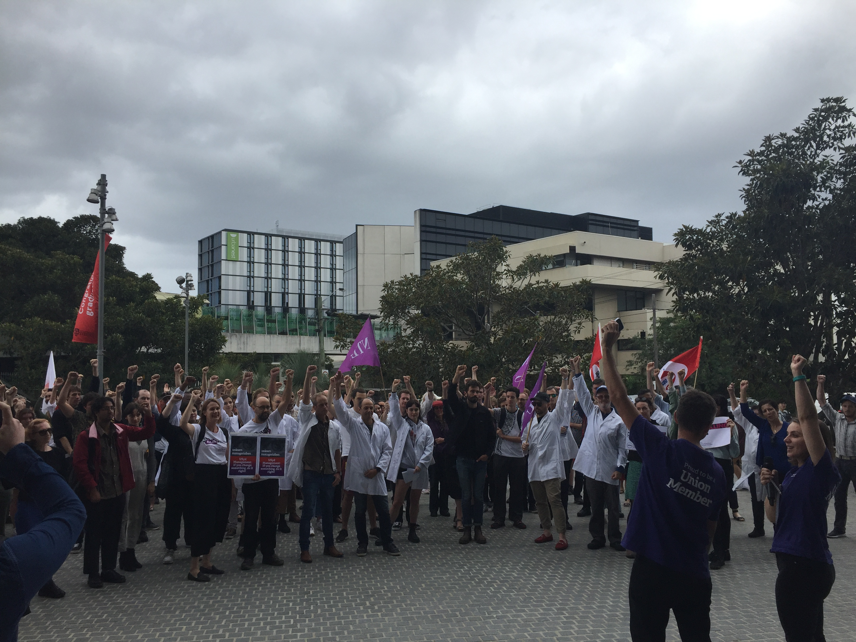 An NTEU motion of no confidence against Michael Spence and senior management passed unanimously. Staff and students pictured with fists raised.