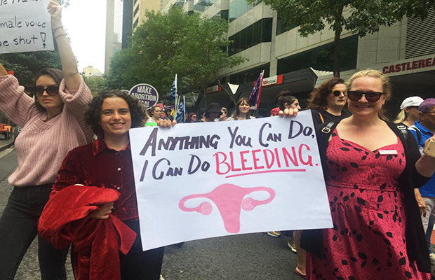"The march makes its way to Belmore Park in Sydney's CBD. Protesters hold a sign which reads ""Anything you can do, I can do bleeding."""