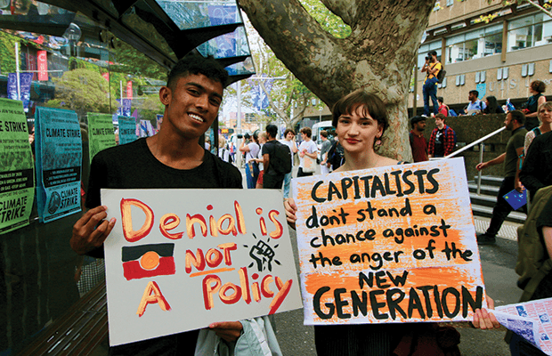 "Jazz Breen, Wm*ns collective convenor and USyd student Seth Dias hold up signs that read ""Denial is not a policy"" and ""Capitalists don't stand a change against the anger of a new generation."" Photo by Amelia Mertha."