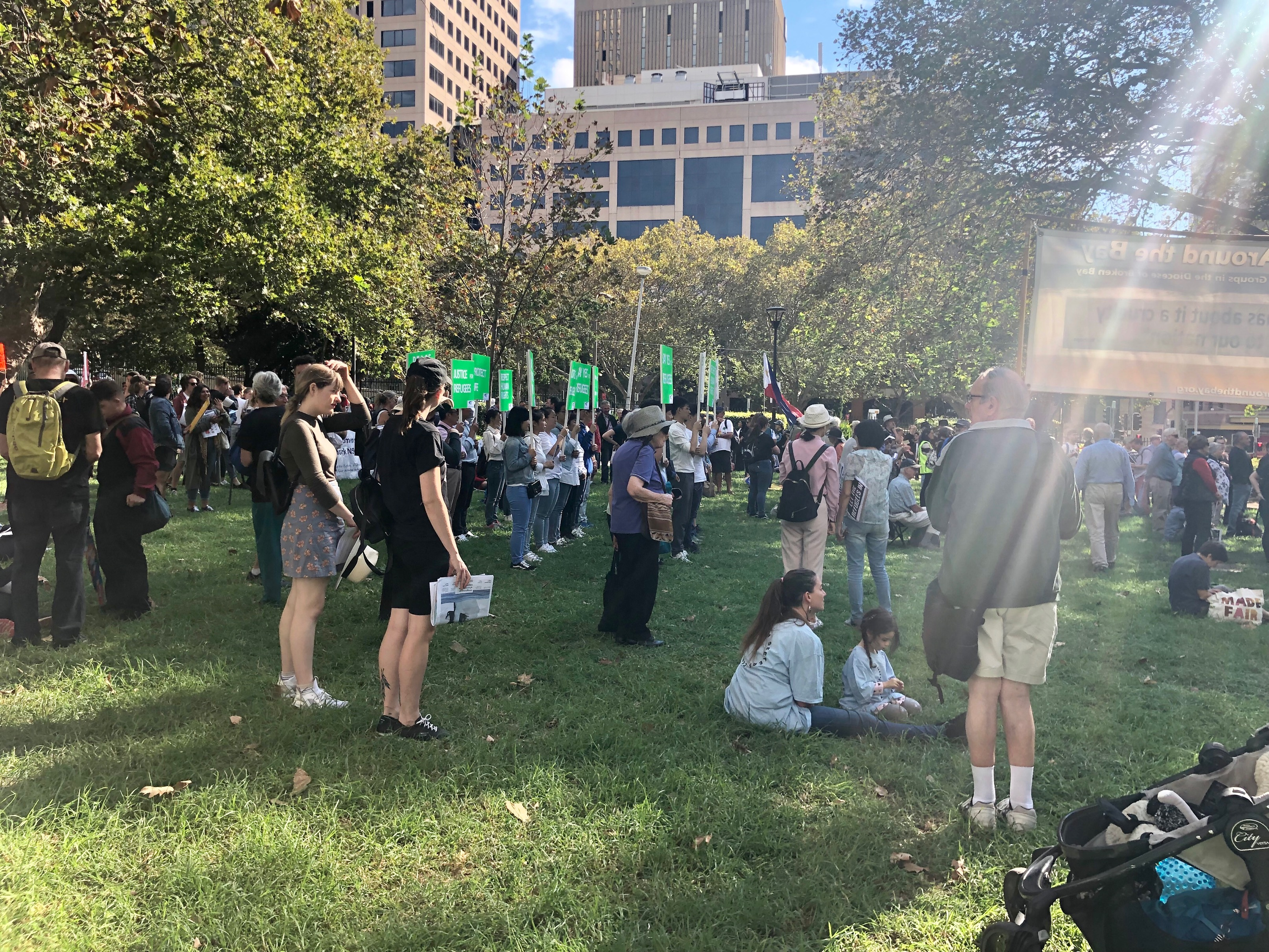 "Protesters meet in Belmore Park holding green placards that read ""Justice for Refugees"""