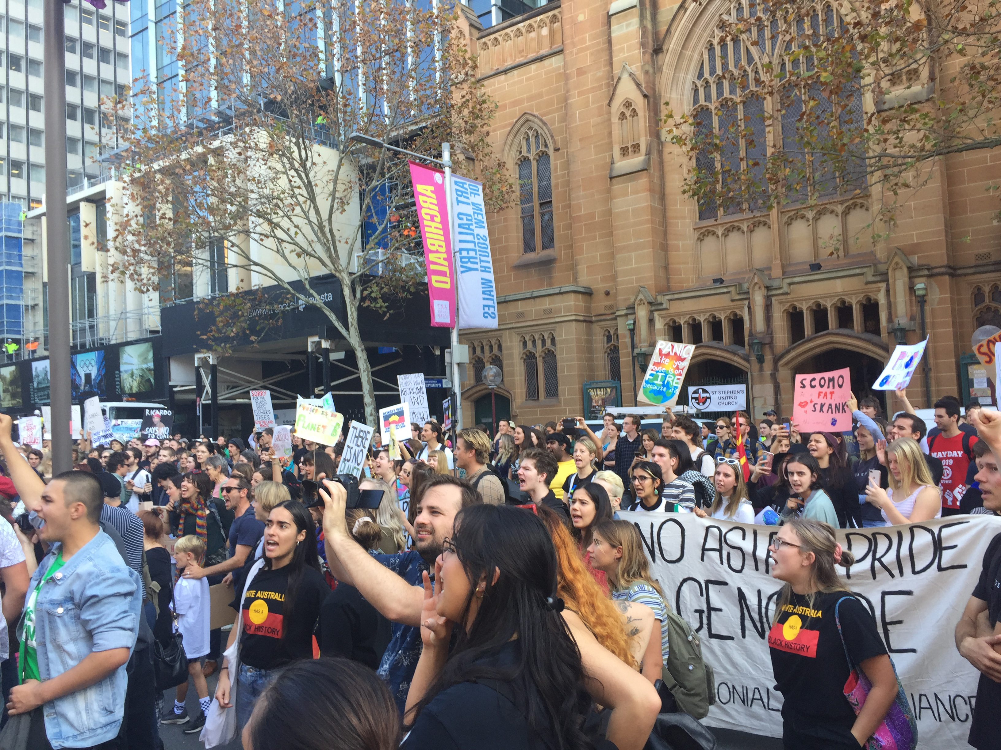 "A mid-crowd shot taken outside NSW Parliament House. In it is a banner reading ""No Asian Pride In Genocide"""
