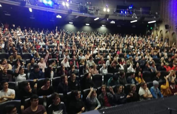 A photo of 500 students gathered in an auditorium all raising their hands
