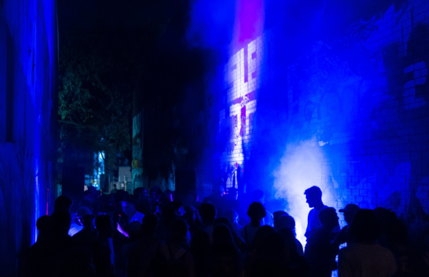 Image: Alley way from a hardcore event, bathed in a blue light.