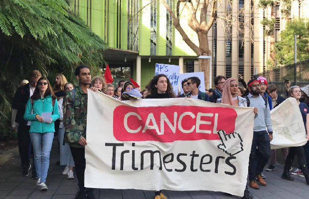 "A photo of students marching at UNSW holding a banner that reads ""cancel trimesters""."