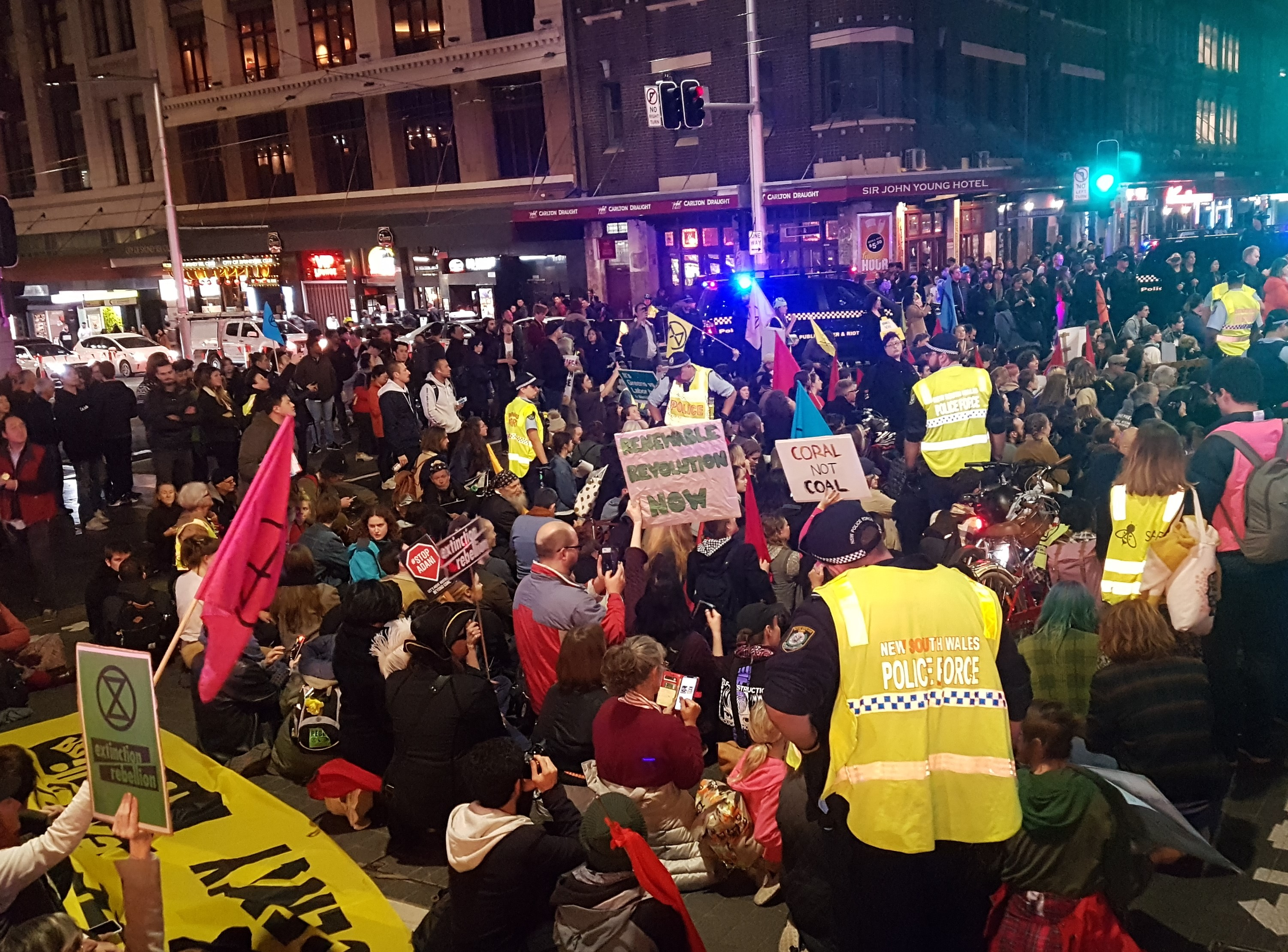 Activists sit down on the road at the intersections of George St and Liverpool St.