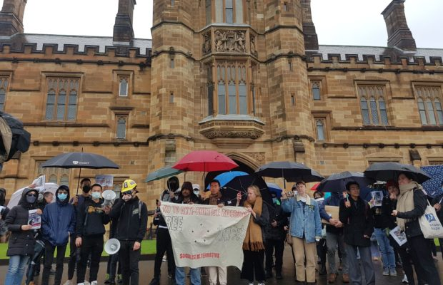 "Protesters chant outside the University Quadrangle. Members of the Socialist Alternative hold up a banner which reads ""No to Anti-Chinese Racism"" and ""Free Hong Kong"""
