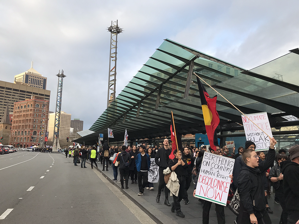 "Protesters line up along the road at the Railway Square bus stops. Several Aboriginal flags are pictured, and two signs are at the front of the image. One reads ""Birthing on country is a human right, decolonise now"", and another reads ""No climate justice without Blak justice."""