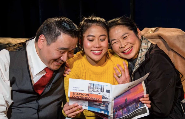 Photo of the three main characters of a deal on a couch reading a real estate magazine