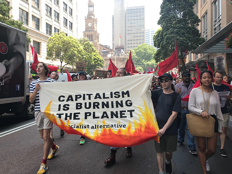 "Marchers carry a banner that reads ""CAPITALISM IS BURNING THE PLANET: socialist alternative."" With flames painted on the bottom."
