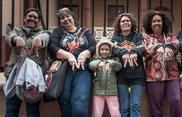 Four Aboriginal grandmothers and a young Aboriginal girl are smiling at the camera and making the letter 'M' with their hands