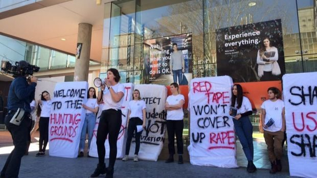 "Members of the 2016 Women's Collective protesting outside the Law Annex building. They carry mattresses spray painted with slogans lie ""Red tape won't cover up rape""."