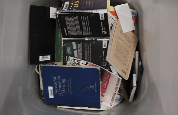 A photo of some books in a bin ready to be shredded.