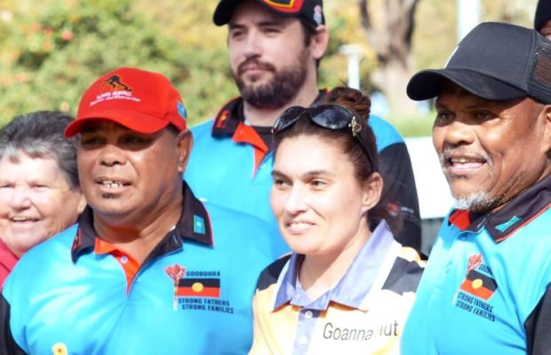 Smiling Indigenous Australians and allies standing together in a crowd.