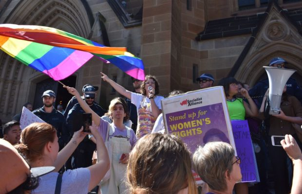 "Colourful protestors standing on the steps of St Mary's Cathedral, waving the rainbow pride flag while chanting: ""Women will decide our fate, not the Church not the State""."