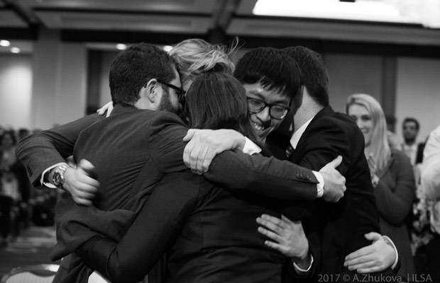 A photo of the winning team hugging.