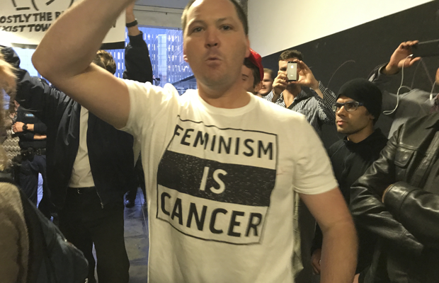 "A man wearing a shirt that reads ""feminism is cancer"""