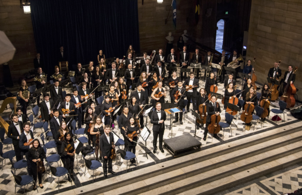 The Sydney University Symphony Orchestra. A large group of young people dressed in black, seated in semi circle rows radiating from the conductor's stand. They are all standing up to take a bow at the end of the performance.
