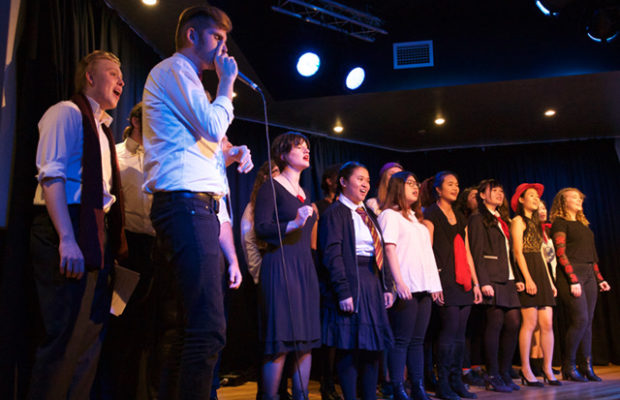 A group of young people stand in two lines on stage, lit by stage lights. The man at the front on the left is holding a microphone and is beatboxing while the rest sing.