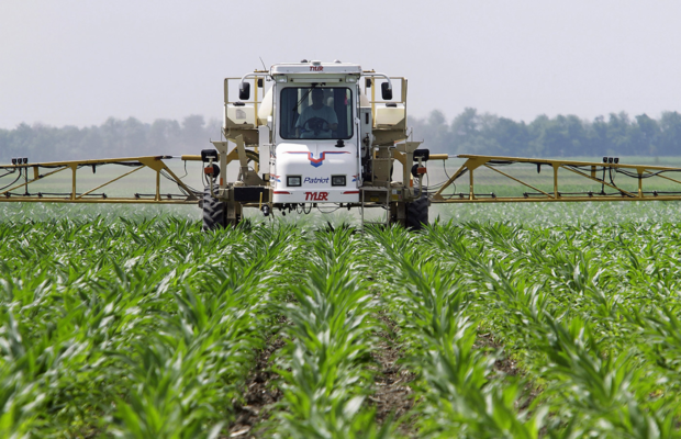 picture of agricultural vehicle spraying pesticides on GM crops