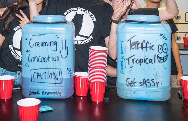 Two blue plastic containers labelled with various punch recipes, red drinking cups centred, students wearing SASS t-shirts in the background