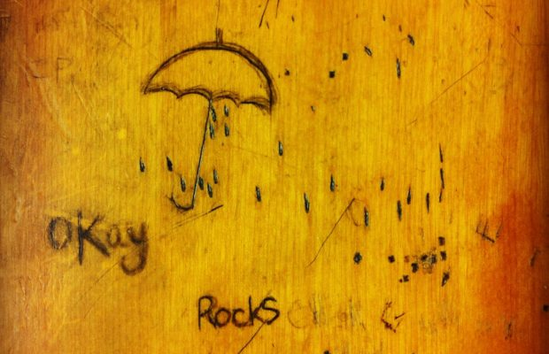 Light brown wooden desk surface, graffiti inscribed with ballpoint pen, umbrella and writing 'okay' and 'rocks'